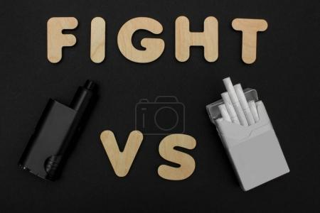 Cigarettes against Vape. Electronic cigarette over a dark background. Popular devices of year - modern vaping device.