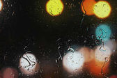 Raindrops on a car window with beautifully blurred background of street traffic lights