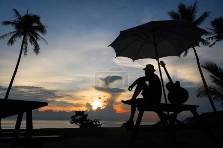 Man playing guitar on the beach with blue sky sunrise