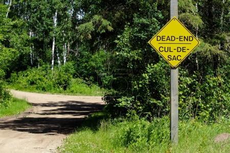 Photo pour Un panneau d'impasse à côté d'une route de gravier . - image libre de droit