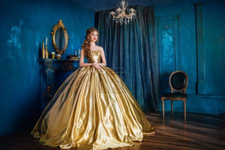 Photo for Beautiful woman in a golden ball gown in the great blue interior - Royalty Free Image