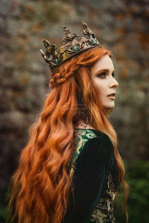 Photo pour Femme rousse vêtue d'une robe médiévale verte près du château - image libre de droit