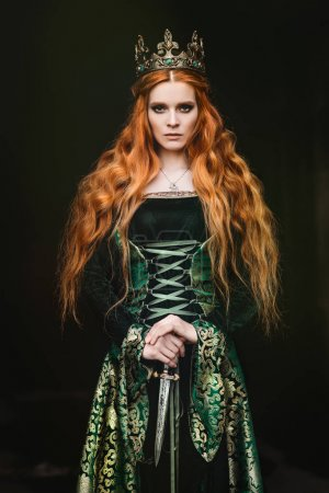 Photo for Portrait of a beautiful red-haired woman in green medieval dress - Royalty Free Image