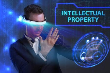 Photo pour Concept de Business, technologie, Internet et réseau. Jeune homme d'affaires travaillant sur un écran virtuel de l'avenir et voit l'inscription: propriété intellectuelle - image libre de droit