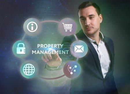 Photo pour Concept de Business, technologie, Internet et réseau. Jeune homme d'affaires travaillant sur un écran virtuel de l'avenir et voit l'inscription: gestion immobilière - image libre de droit