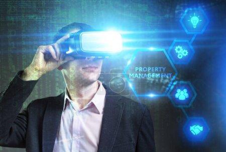 Photo pour Concept de Business, technologie, Internet et réseau. Jeune homme d'affaires travaillant dans les lunettes de réalité virtuelle voit l'inscription: gestion immobilière - image libre de droit