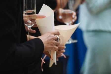 Photo for Women standing with glasses of white wine and paper cones - Royalty Free Image
