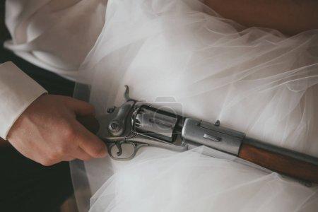 Photo for Man holding gun on white bridal dress - Royalty Free Image