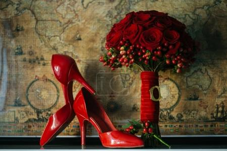 Photo for Red wedding bouquet and pair of heels on brown background - Royalty Free Image