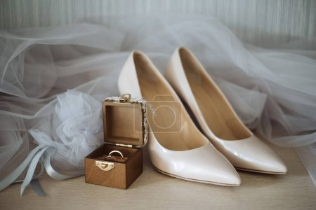 Photo for High heeled shoes and wedding rings box with bridal veil on background - Royalty Free Image
