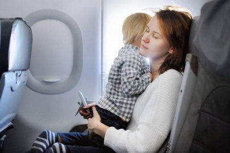 Photo pour Jeune femme voyageant avec son petit enfant par un avion. Garçon enfant assis avec sa mère fatiguée par la fenêtre de l'avion. Concept de la maternité - image libre de droit