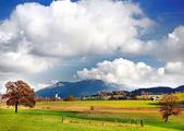 Scenic view of typical Bavarian lansdcape with cloudy blue sky on sunny autumn day