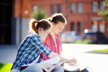 Young happy students with books and notes outdoors