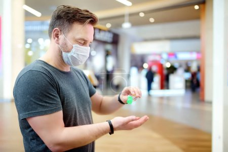 Photo for Man wearing disposable medical face mask makes disinfection of hands with sanitizer in airport, supermarket or other public place. Safety during coronavirus outbreak. Epidemic of virus covid. - Royalty Free Image