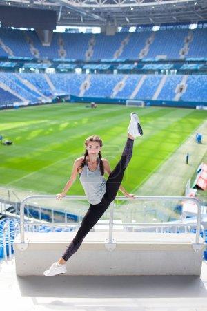 Photo pour Jeune fille sportive a sauté haut et écarté les jambes dans différentes directions sur le fond d'un stade de football. Femme en vêtements de sport un grand étirement . - image libre de droit