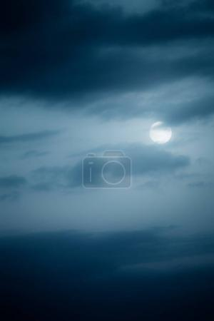 Bright white moon on dark night sky with black clouds