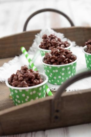 Closeup of green paper cups with rice crispies covered with milk chocolate on white wooden table