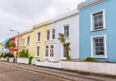 street in a seaside town, with colorful facades of buildings, en