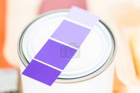 Paint swatches with purple paint sample and metal can with paint.