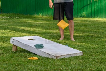 Photo for Low angle action shot of corn hole game in backyard at family party in summertime - Royalty Free Image