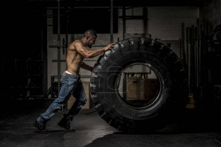Muscle Man in Jeans Pushing Large Tire