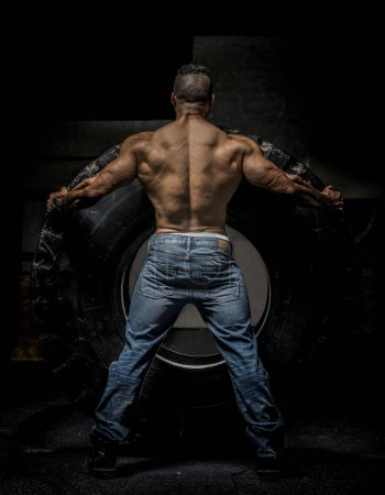 Man showing muscular back with large tire