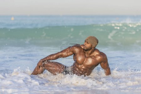 man sitting in water on edge of beach