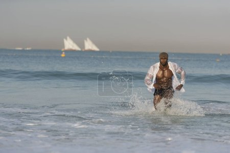 man running on edge of beach