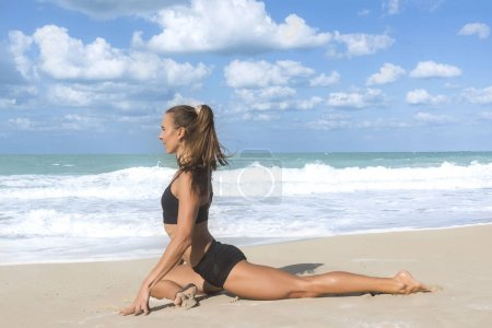 White European girl in a yoga pose on beach with black tight shorts and black top on a bright sunny day with blue skies and white fluffy clouds