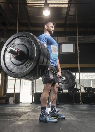 Photo for Strong white man deadlift some really heavy weights in cross-fit  gym with an aggressive face - Royalty Free Image