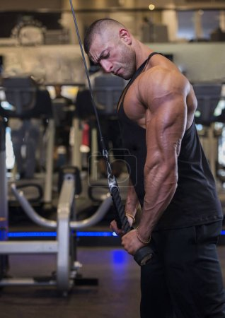 bodybuilder doing triceps workout with rope