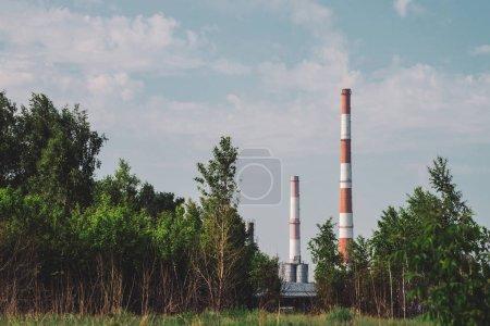 Photo pour Stack de fumée géante dans la zone industrielle derrière les arbres. Structure industrielle avec gros tuyau de brique brune sous le ciel bleu - image libre de droit