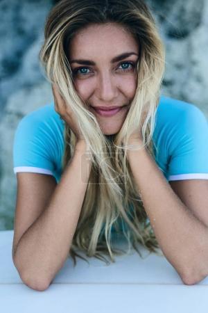 Photo pour Gros plan d'une belle jeune femme avec tête sur mains relaxants sur la plage - image libre de droit
