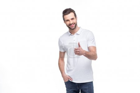 Photo pour Handsome young man showing thumb up and smiling at camera isolated on white - image libre de droit