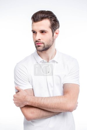 Photo pour Handsome young man in white polo shirt looking away isolated on white - image libre de droit
