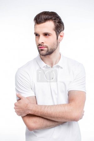 Foto de Handsome young man in white polo shirt looking away isolated on white - Imagen libre de derechos