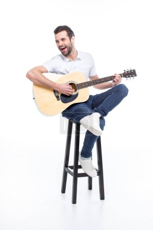 Photo for Laughing young man playing guitar while sitting on stool  isolated on white - Royalty Free Image