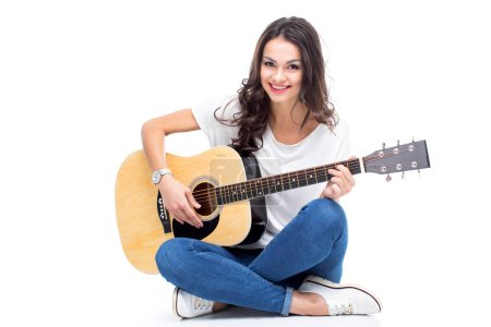 Photo for Smiling young woman sitting and playing guitar isolated on white - Royalty Free Image