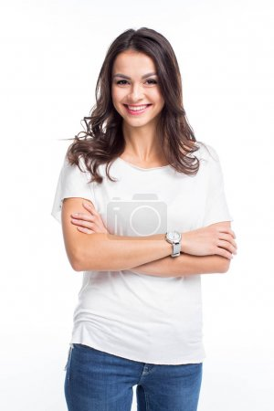 Photo pour Attractive young woman standing with crossed arms and smiling at camera isolated on white - image libre de droit