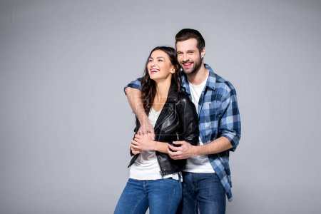 Photo for Beautiful young couple standing embracing and smiling isolated on grey - Royalty Free Image