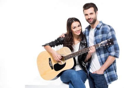Photo pour Beautiful young couple with acoustic guitar smiling at camera  isolated on white - image libre de droit