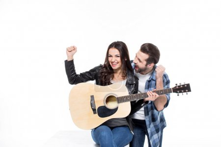 Photo for Excited young couple sitting with guitar and triumphing  isolated on white - Royalty Free Image