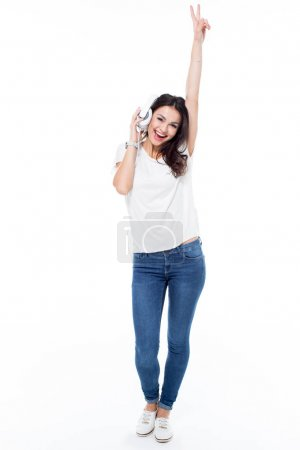 Photo pour Excited young woman pressing headphones to ear and listening to music isolated on white - image libre de droit