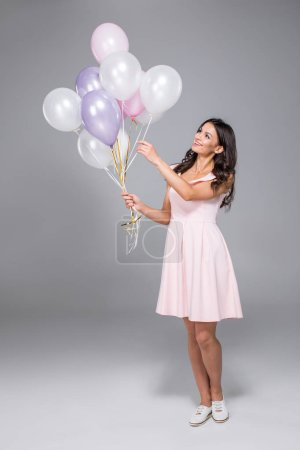 Photo for Young gorgeous woman in dress holding bunch of air balloons isolated on grey - Royalty Free Image