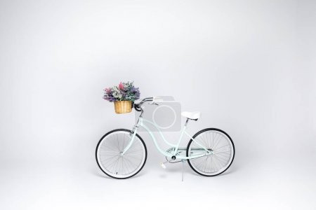 Photo for Hipster bicycle with basket  full of fresh flowers isolated on white - Royalty Free Image