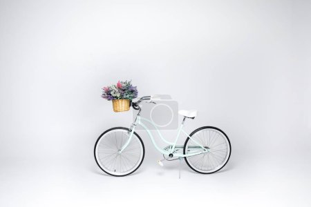 Foto de Hipster bicycle with basket  full of fresh flowers isolated on white - Imagen libre de derechos