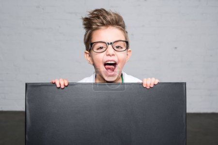 Photo for Excited little boy in eyeglasses holding blank blackboard and looking at camera - Royalty Free Image