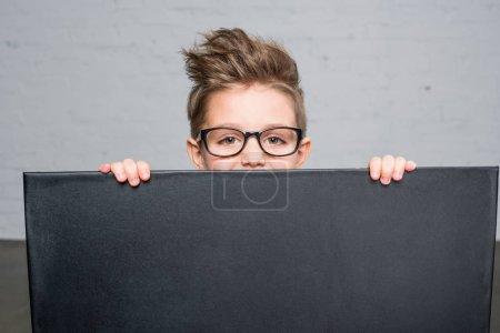 Photo pour Mignon petit garçon dans les lunettes tenant tableau noir vierge et regardant la caméra - image libre de droit