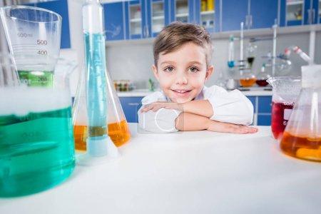 Photo pour Mignon petit garçon penché à la table et souriant à la caméra dans le laboratoire chimique - image libre de droit