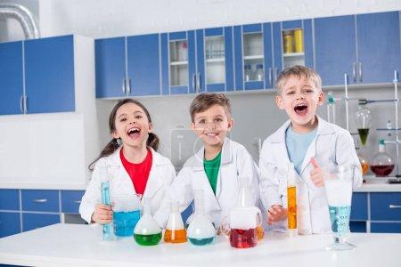 Photo pour Trois enfants heureux en manteaux blancs faisant des expériences chimiques en laboratoire - image libre de droit